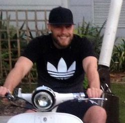 Dale Hart, a white man wearing a black cap and shorts and a black T-shirt with a white Adidas logo, sitting on a white scooter.