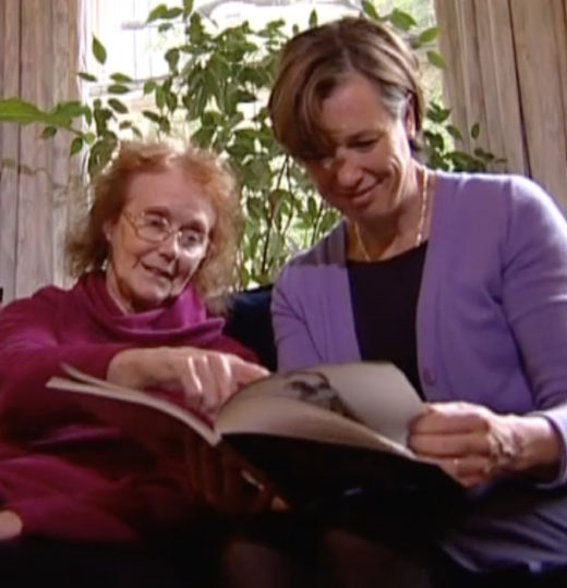 Picture of Elaine McDonald, an elderly white woman with red hair wearing a pink jumper, sitting next to a younger white woman wearing a purple jacket over a black top, holding a book at which Elaine McDonald is pointing.