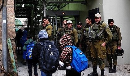 Three children with school bags entering a tunnel, passing by a group of armed Israeli soldiers.
