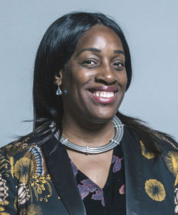 Portrait of Kate Osamor, a Black woman wearing a necklace consisting of 3 solid metal bands, with a top consisting of yellow shapes on a black background.
