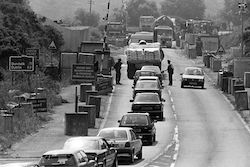 A black-and-white picture of a checkpoint on the main Belfast-Dublin road some time during the Troubles. Cars and trucks are queueing, there is a raised barrier and soldiers or police are standing at a driver's window apparently inspecting a document. There are concrete blocks at regular intervals on both sides of the road. A distance sign gives the road number A1 and distances to Dundalk and Dublin.