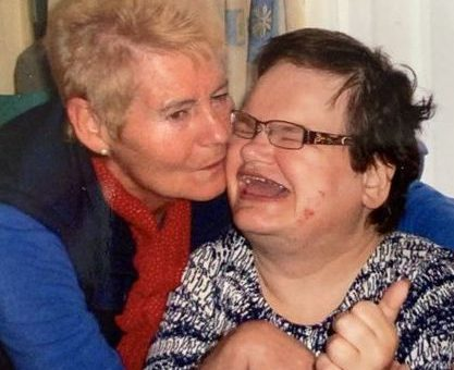 Picture of two white women, an older woman kissing her middle-aged daughter who is wearing a blue and white patterned top.
