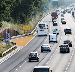 A motorway with four lanes and no hard shoulder. A small refuge area can be seen on the left: a short lay-by with yellow paving. The road is busy with cars, vans, coaches and trucks.
