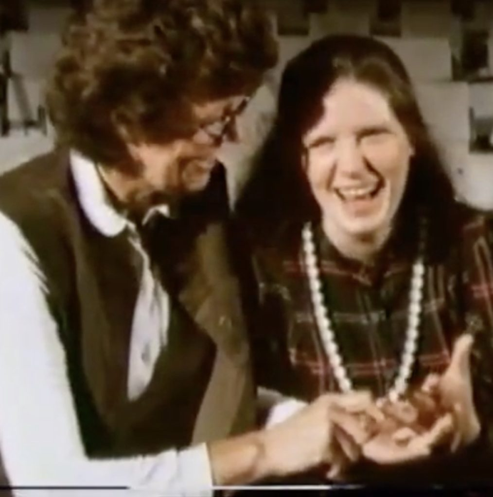 Janis Revell, a young white woman with long dark hair wearing a plaid shirt with a long necklace of pearls hanging from her neck, smiling as an older woman (her mother, Audrey Revell) spells something into her hand.