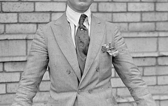 Black and white picture of Charles Ponzi, a white man dressed in a suit and tie with a wide-rimmed hat, holding a walking stick in his hands.