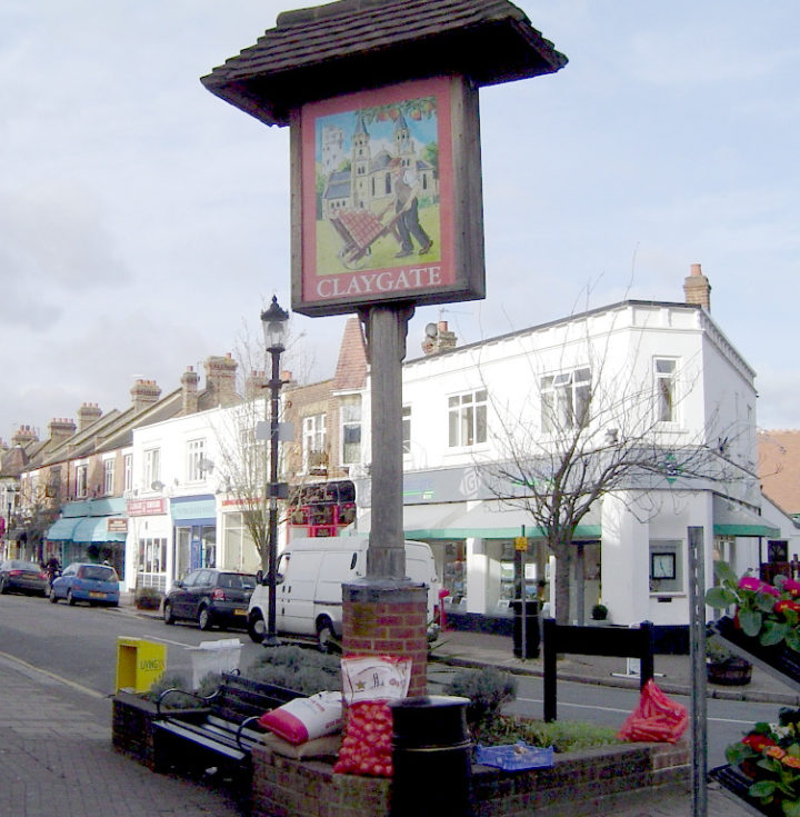 Picture of a village sign showing a church and a man pushing a loaded barrow across grass in front of it; the sign stands on a pole amid a flowerbed surrounded by benches and a roadsign facing the other way. There is a parade of shops across the road which stretches from a corner behind the sign, including a florist with flowers displayed outside at the shop on the corner.