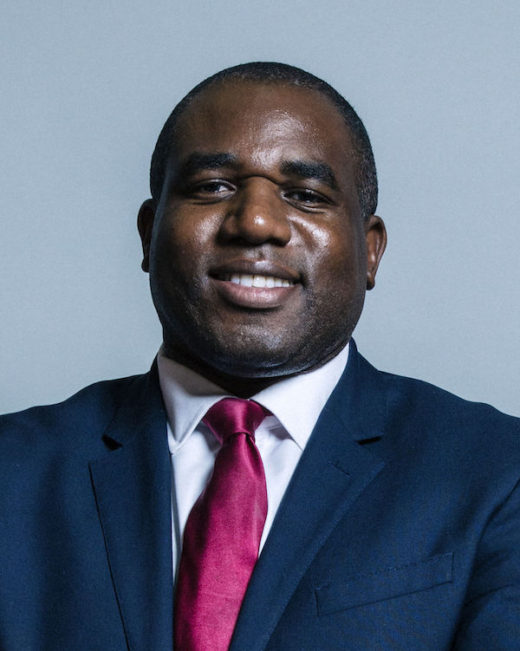 Picture of David Lammy, a Black man with very short hair wearing a white shirt, a shimmering red tie with a dark blue jacket over the shirt.