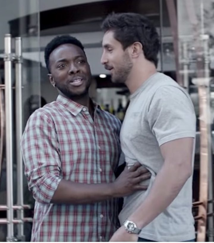 A still from a Gillette video in which a Black man is stopping a man of Latino appearance outside a shop, putting his right hand on the man's lower abdomen.