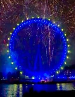 The London Eye, a ferris wheel, lit up in blue with yellow lights round the outside (as on the European flag). Traces of other fireworks can be seen around it. The lights are reflected in the River Thames at the bottom.