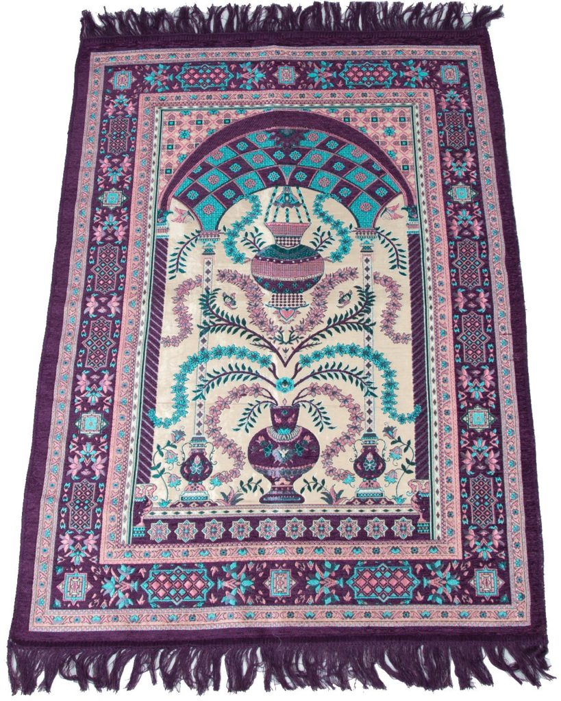 A rectangular prayer mat in purple and turquoise, with an image of vases with branches coming out of them and of an ornament hanging from an arch at the far end. There are purple tassels at each end.