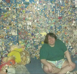 A picture of Stephanie Bincliffe, a young, very overweight white woman wearing a green T-shirt and a pair of shorts, sitting against a wall decorated in many colours with some cuddly toys sitting on the floor next to her.