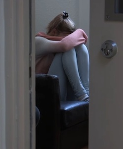 A young girl sits on a black, leather (or faux leather) sofa behind a partially open door. She has her knees raised to her face and her arm covering the rest of her face. She is wearing a white and pink jumper and light blue jeans or tracksuit bottoms.