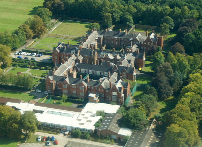 Aerial view of a large Victorian hospital with three courtyards set in fields with banks of trees on the right.