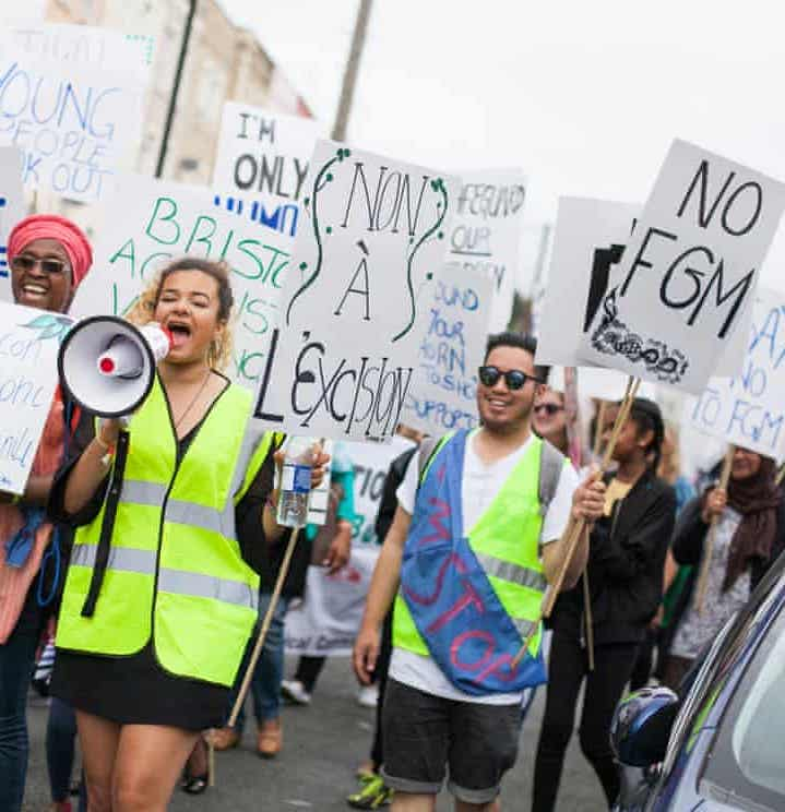 A group of demonstrators in the street holding placards with slogans in various languages against FGM.