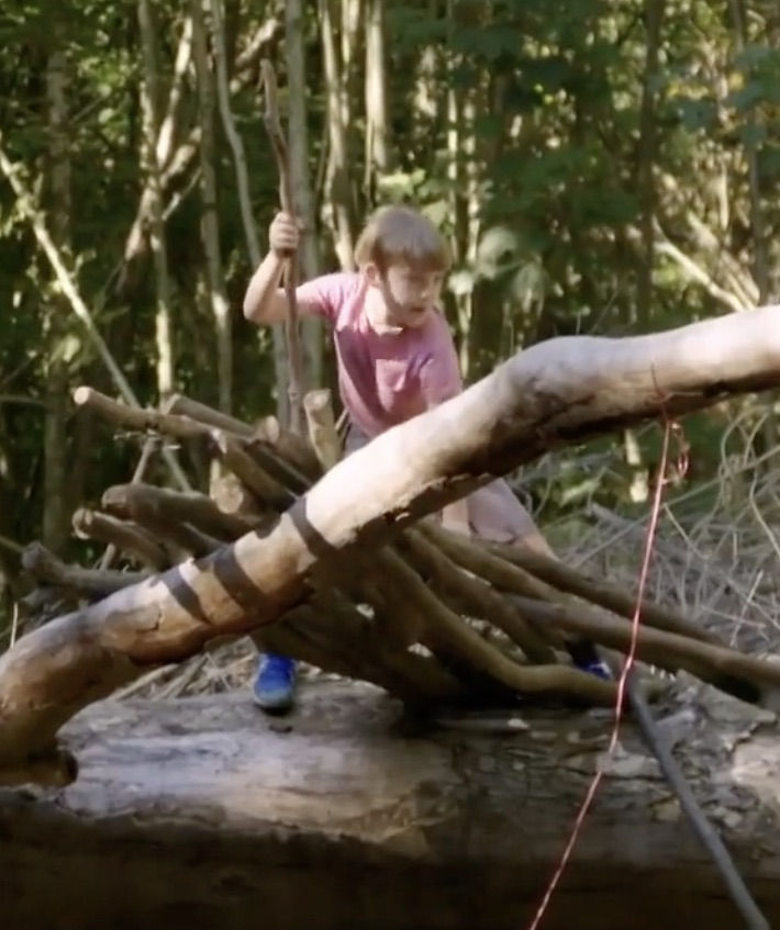 A young boy wearing a pink T-shirt holding a wooden stick vertically in his hand, playing on a set of wooden logs stood against a tree branch.