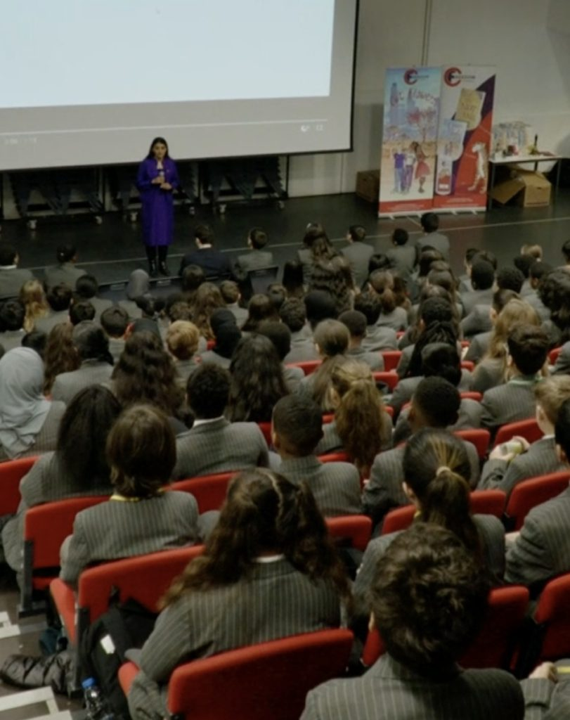 "A South Asian woman wearing a dark blue dress stands in front of a projector screen next to a poster from the FGM ""Freedom Project"" in a school auditorium. Teenage boys and girls in school uniforms with grey blazers sit in the ranks of red seats."