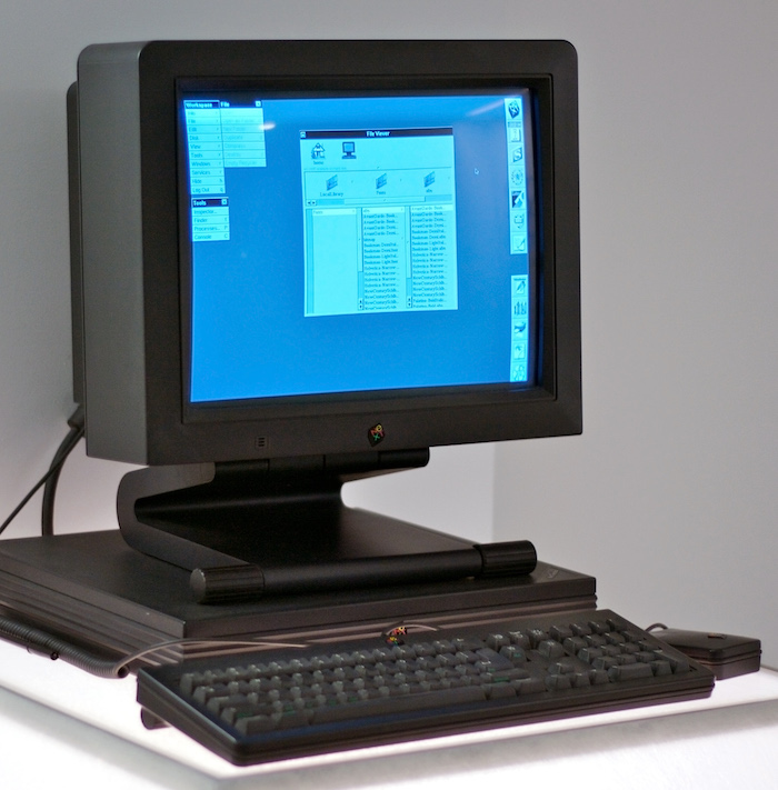 A black desktop computer consisting of a keyboard, a low-profile system unit and a colour monitor on which several menus, a file manager window and a dock of icons down the right-hand side of the screen can be seen.