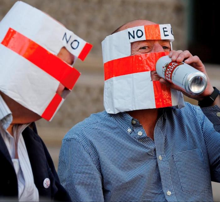 "Two white men, both wearing white masks with the red St George's cross on it, with ""NO EU"" around the forehead. One of them is drinking from a can of Stella Artois beer. (Stella Artois is Belgian.)"