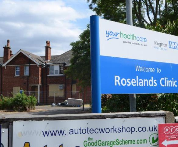 "A boarded-up, two-storey, red-brick building with concrete blocks and metal fencing in front of it. In the foreground is a blue sign that says ""Welcome to Roselands Clinic"", and above it, on a white background, the logos ""Your Healthcare, providing services for the NHS"" and ""Kingston NHS Primary Care Trust""."