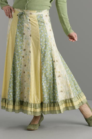A woman wearing an ankle-length skirt with panels of yellow, beige and light green with flower patterns on the beige and green. There are three bands, two green with yellow in between, at the hem. She is wearing a light green jumper but her head and torso are cropped out.