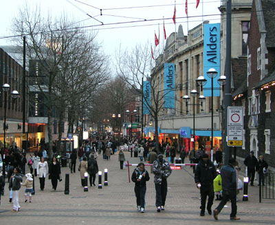 "A look down the shopping street North End, in Croydon, on a February day in 2005 with still-bare trees. On the left is the stone facade of Allders with blue on cyan signage; other shops further back are obscured by the trees. On the left can be seen the vertical lettering of Debenhams. In front of Debenham's on the right is a sign saying ""Pedestrian Zone: No Vehicles"" followed by loading exemptions. The tram lines cross in the foreground and their overhead wires are above."
