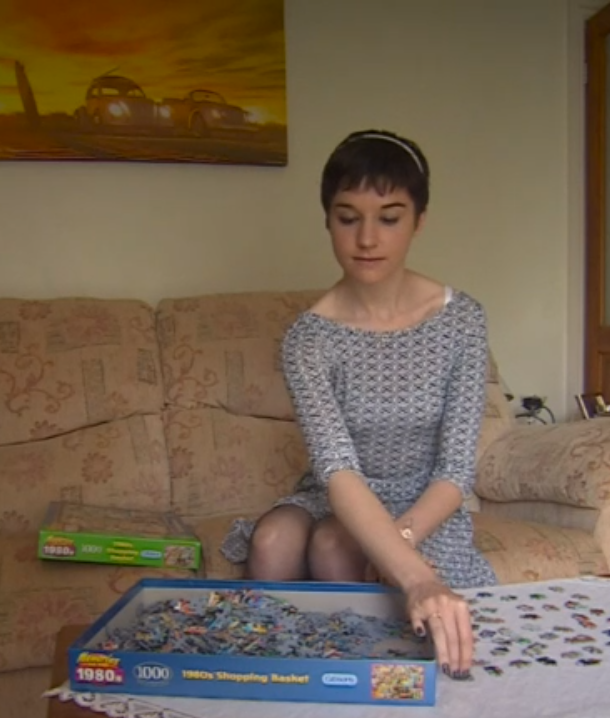 "A picture of Claire Greaves, a young white woman wearing a loose but short grey patterned dress, doing a jigsaw puzzle based on an ""1980s shopping basket"" theme."