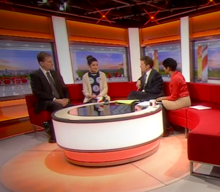 A still from a BBC TV programme showing four adults (two male, two female) sitting on a semicircular red sofa round a glass-topped table. Claire Greaves is second from left.