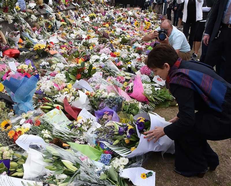 A large array of bunches of flowers lying on the ground and against a wall on the left. A white woman dressed in a black suit kneels down to lay another bunch on the ground, as a balding white man stands with a Canon SLR camera to take a picture of her.