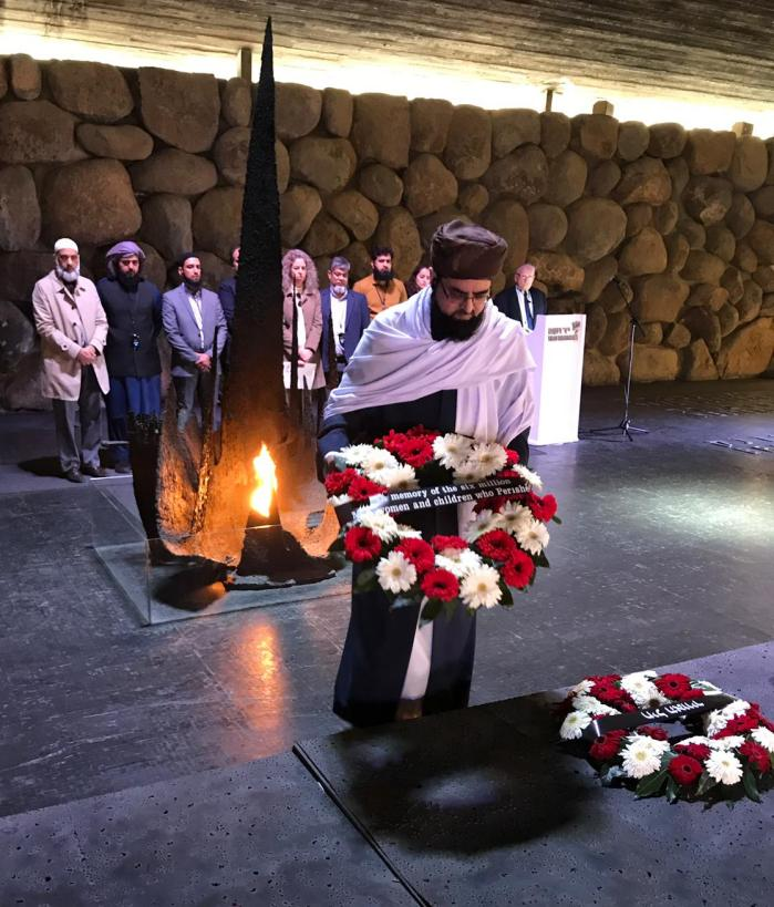"A South Asian imam with a large black beard, wearing a brown turban with a white shawl around his upper chest, lays a wreath of red and white flowers in front of a monument to ""the memory of the six million men, women and children who perished"" (in the Holocaust). A line of nine or ten people, mostly men, including other imams stand behind him against a wall of large stones. A fire stands behind him with a jagged 'finger' pointing up out of it."