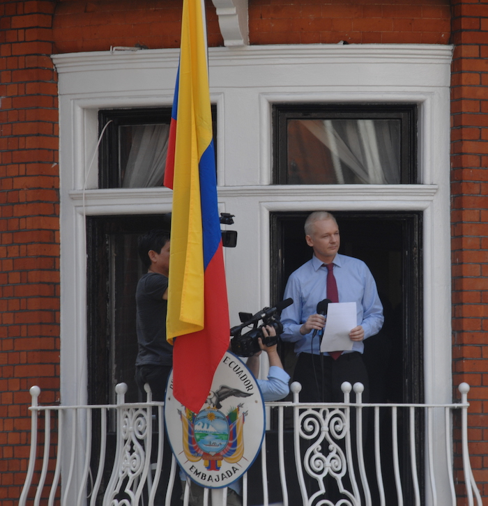 "A white man with blond hair wearing a light blue shirt and red tie, standing at a French window behind a balcony holding a piece of A4 white paper and a microphone. The yellow, blue and red flag of Ecuador hangs from a flagpole with the coat of arms below with the words ""Republica del Ecuador: Embajada"" around it. Two people are holding cameras pointing at Assange from the left side of the balcony."