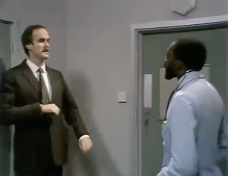 Basil Fawlty (John Cleese) recoiling from a Black man in a white coat with a stethoscope round his neck, in the 1970s comedy Fawlty Towers