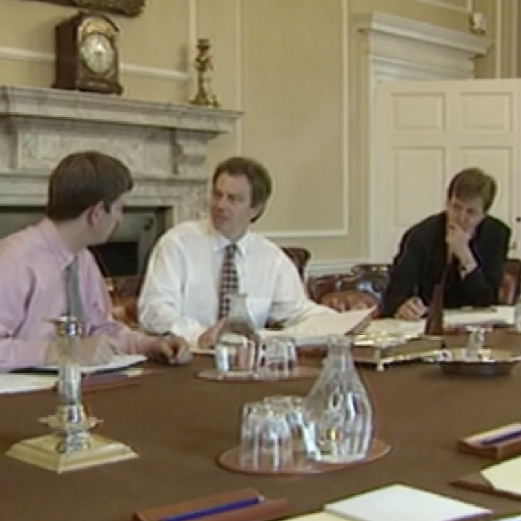 Three white men (including Tony Blair, Alastair Campbell and a third whose face is obscured) wearing suits and ties sitting at a large wooden table with papers in hand. A marble fireplace is behind Tony Blair and the third man.