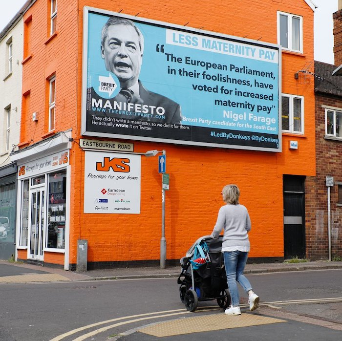 "A poster for the Brexit Party with a statement by Nigel Farage: The European Parliament, in their foolishness, have voted for increased maternity pay"", next to a black-and-white picture of him on a pale blue background, underneath the heading ""Less maternity pay"", and the slogan ""They didn't write a manifesto, so we did it for them. He actually wrote it on Twitter."" The poster is against an orange painted building with a sign ""JKS: Floorings for your home"". In front of the poster, a woman wearing a light grey jumper and blue jeans pushes a baby in a buggy across a road."
