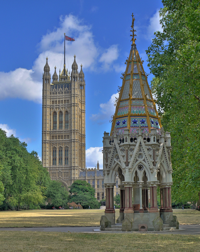 A picture of the Buxton Memorial in the Victoria Tower Gardens; the Houses of Parliament and the Tower itself are in the background. The memorial is a single-storey, octagonal structure with arches on each sides with marble columns. It has a tall, conical roof with coloured stained glass and a gold-coloured cross at the top.