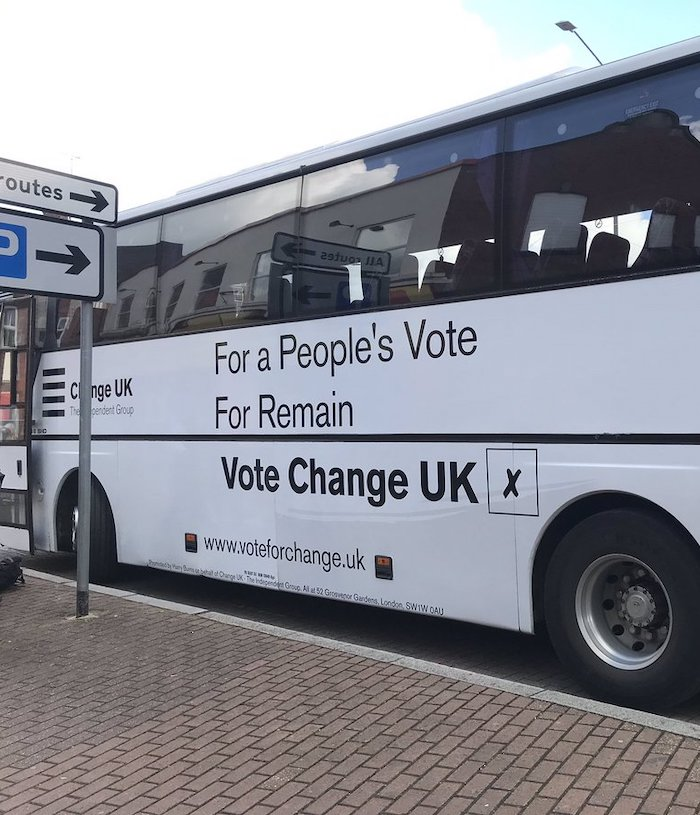 "A picture of a white single-deck bus with the words ""Change UK: The Independent Group. For a People's Vote, For Remain, Vote Change UK"" followed by an X in a black box. In the foreground is a red-brick pavement and a sign pointing to a car park and ""all routes""."