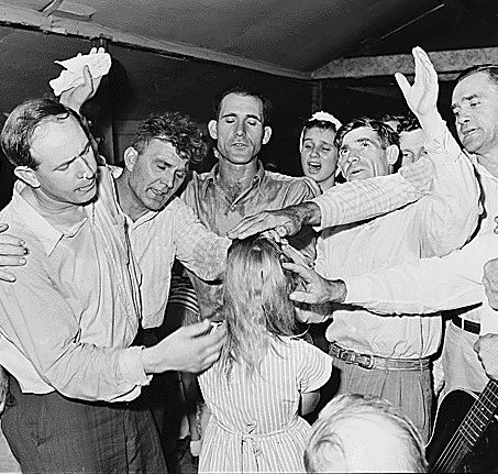 A black and white picture of a group of white men laying their hands on the head of a white woman or girl who is wearing a vertically striped dress and facing away from the camera. A man in the right of the picture is holding an acoustic guitar.