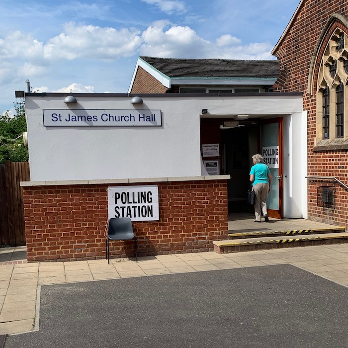 "The back of a church with stained-glass windows, and the entrance to a church hall with the words ""St James Church Hall"" on a rectangular white sign in blue Swiss type. The words ""POLLING STATION"" are on a sign in black bold type with a plastic chair in front. An old lady wearing a turquoise top and grey trousers is walking through the doors which also have a sign saying ""POLLING STATION"" and giving the opening times."