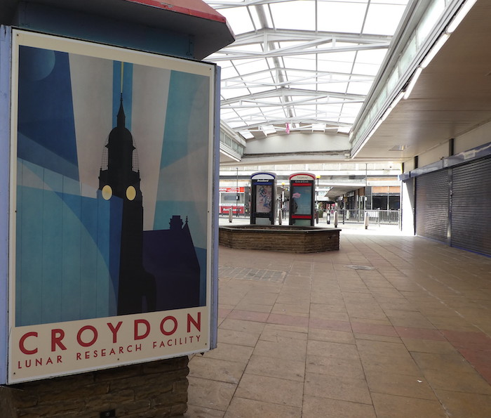 "A picture of a 1970s poster showing a clock tower with lights shining from two sides, with the words in red underneath, ""Croydon lunar research facility"", in a covered walkway with shuttered shops on the right-hand side and two BT phone boxes in the background."