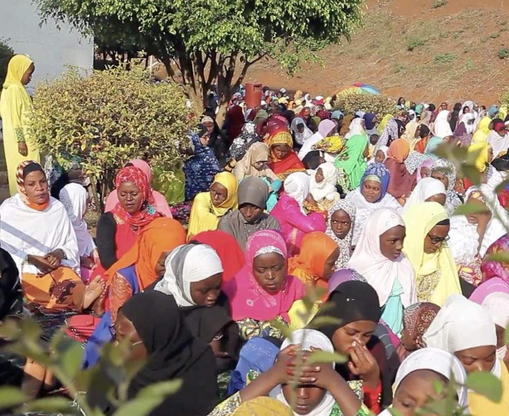 A crowd of Black Muslim women wearing colourful headwraps and dresses in an open area among trees and bushes.