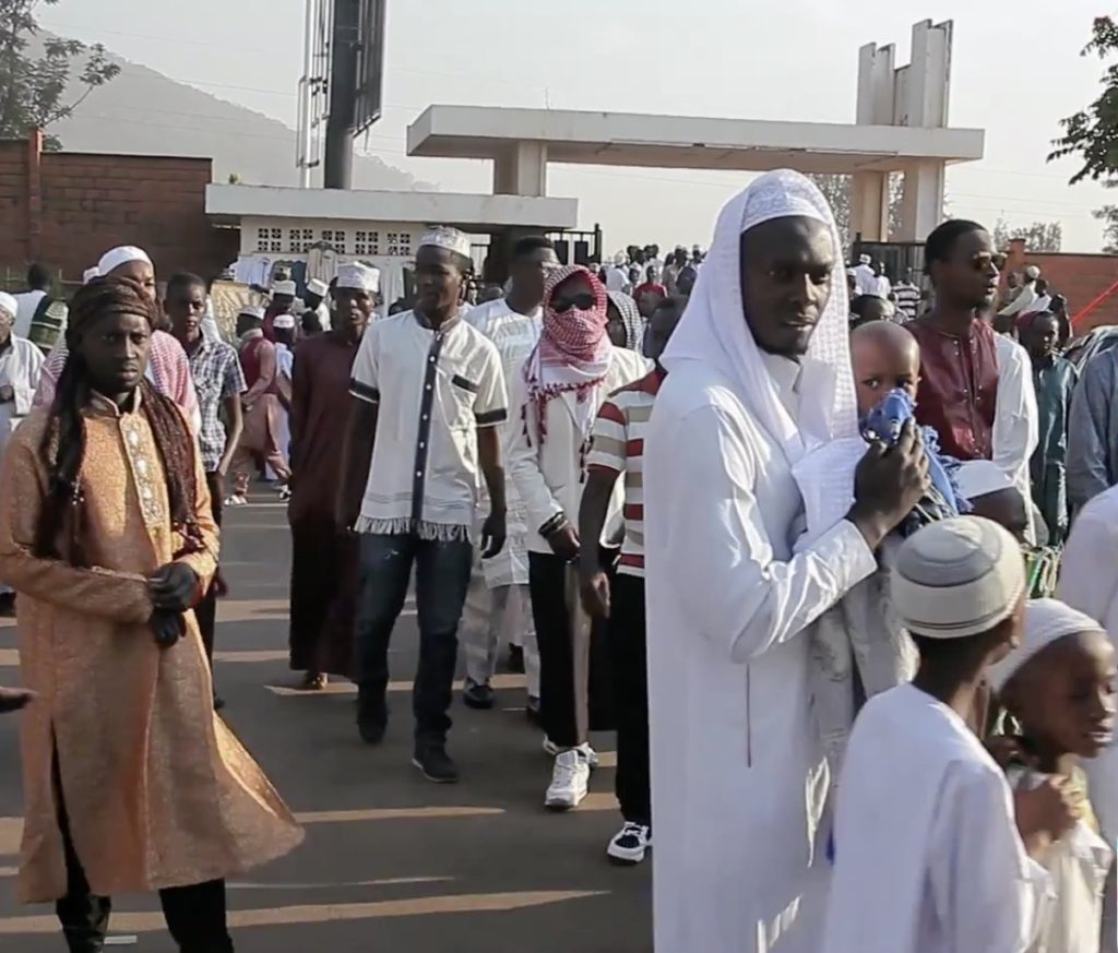 A still from a video showing Muslim men in various Islamic attires such as long robes, keffiyehs and topis coming out of a mosque into a street.