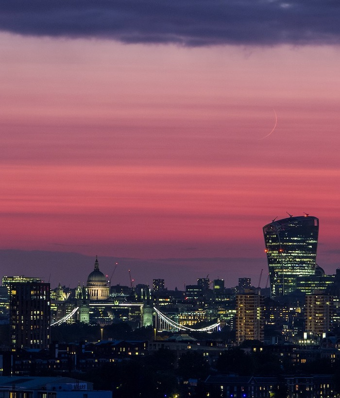 A picture of the new moon in the red evening sky above London; St Paul's cathedral, Tower Bridge and other buildings are lit up below.