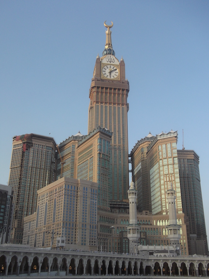A collection of modern skyscraper buildings, the biggest of them a huge office and clock tower with a cupola at the top and the name of Allah in Arabic above the clock face. The sacred mosque and two of its minarets are at the bottom of the image, dwarfed by the modern buildings behind it.