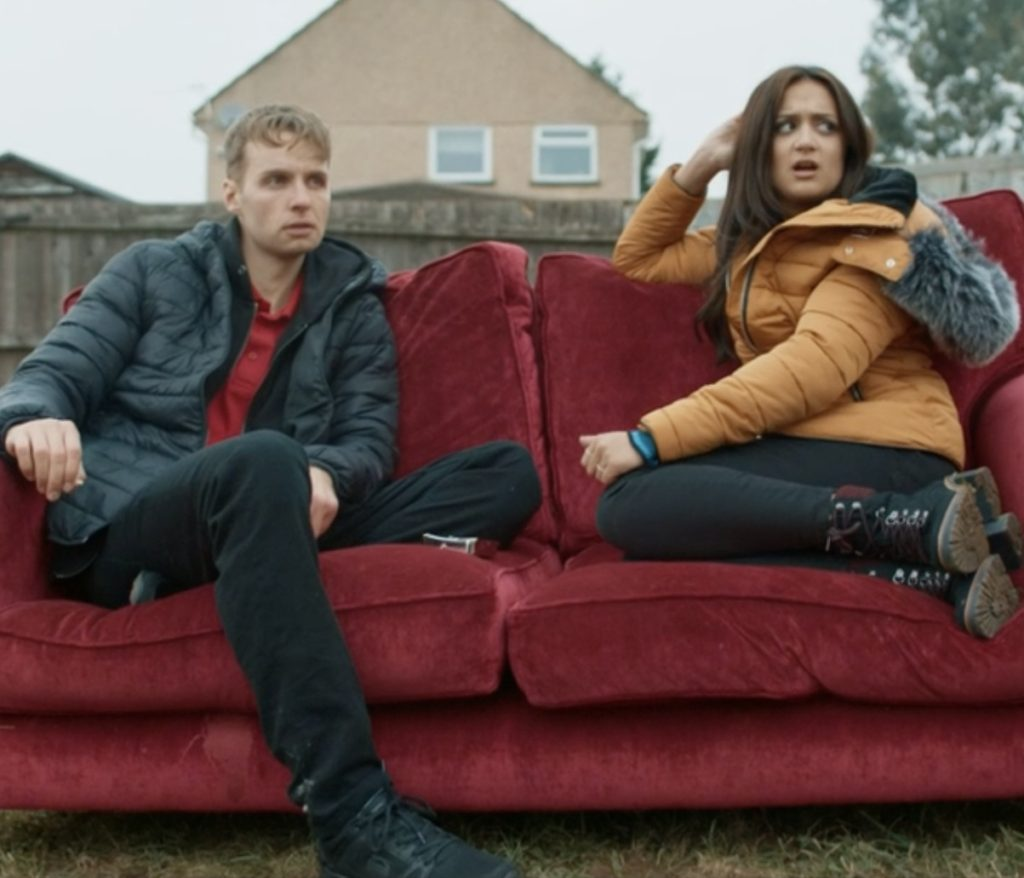 Gethin, a young white man wearing a black jacket and trousers and a red T-shirt sits on a red sofa in the street with a young South Asian woman who is wearing jeans and a yellow jacket. There is a concrete wall behind them, and a new red-brick house behind that.