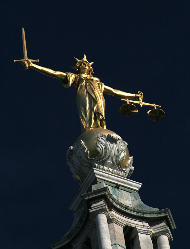 "A photograph of the bronze sculpture of ""Lady Justice"" on top of the Old Bailey criminal court in London, England. The statue has a sword in her right hand and the scales of justice in her left hand."