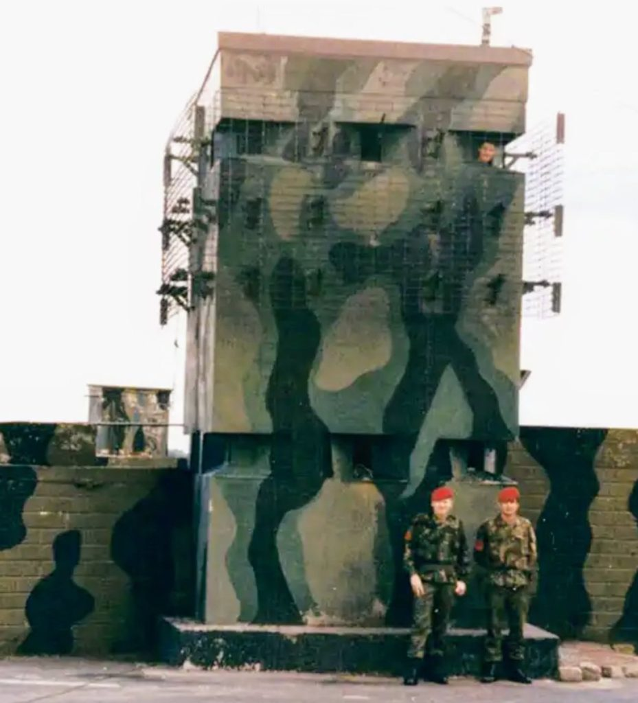A watchtower painted in camouflage colours with a soldier peering out of one of the windows. Two more soldiers, in camouflage uniform with red berets, stand on the ground in front of it. The tower stands between two sections of wall, both painted in the same camouflage colours.