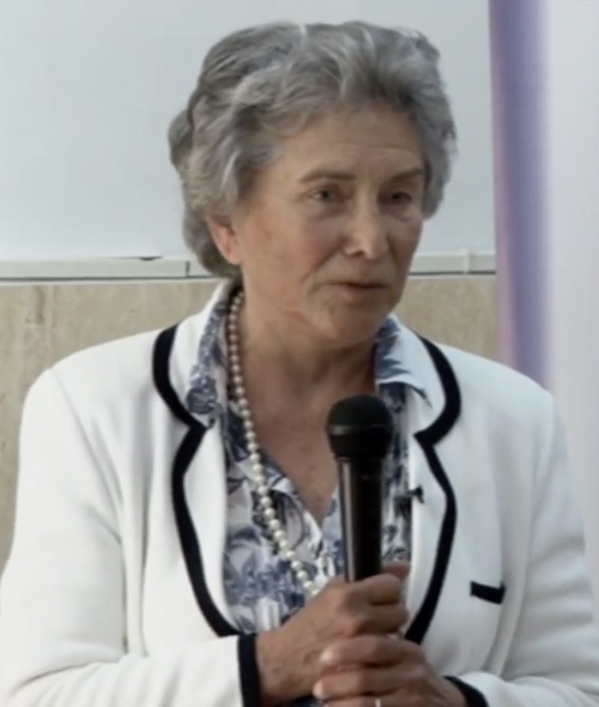 Picture of an elderly white woman with grey hair wearing a blue floral blouse under a white jacket with black edging, holding a black microphone in her hand.