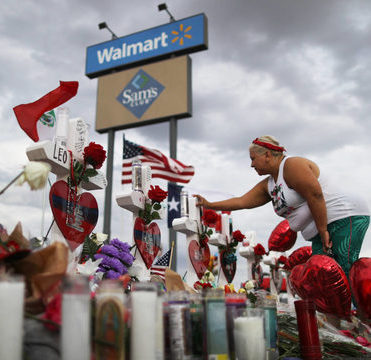 A Walmart and Sam's Club sign, under which are memorials to individuals murdered in the 3rd Aug 2019 massacre, consisting of their names, hearts, flowers and other materials. A woman holding red heart-shaped balloons has her hand on one of the memorials.