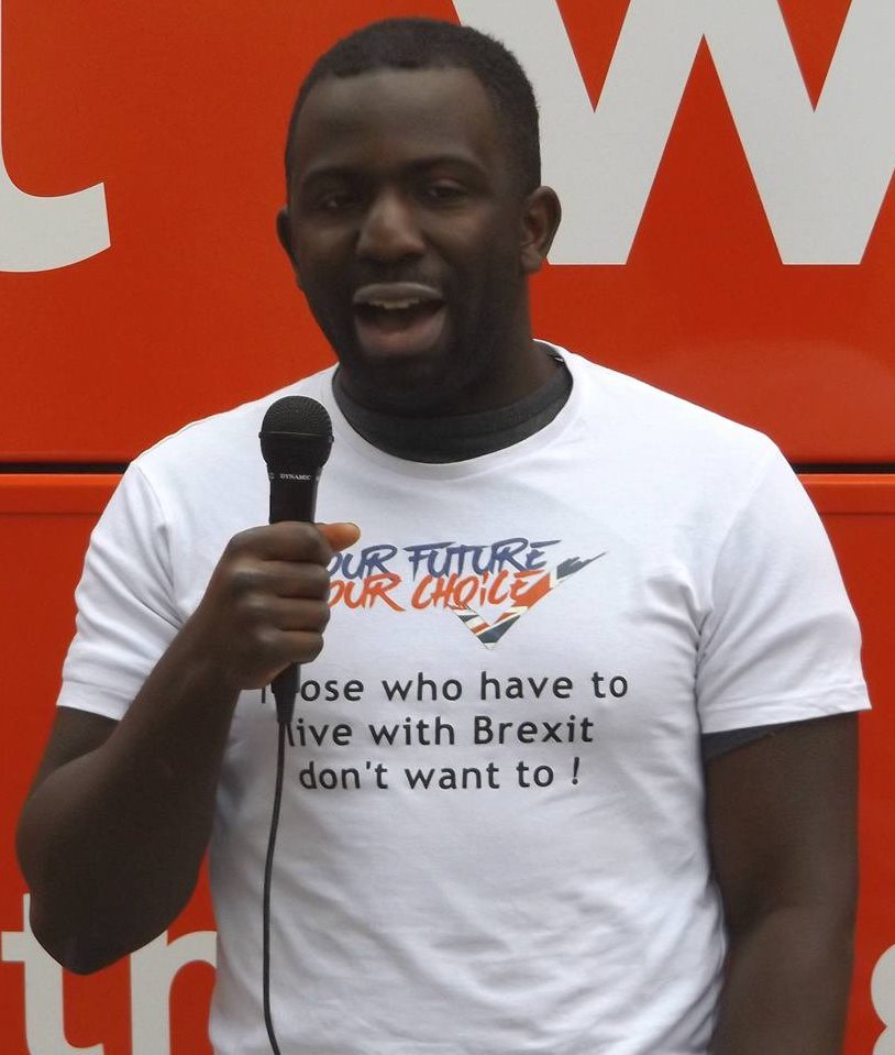 "Picture of Femi Olowale, a young Black man wearing a white T-shirt with the writing ""Our Future, Our Choice: Those who have to live with Brexit don't want to!"". He is holding a microphone and standing against a red background with white writing (too little of which can be seen to know what it says) on it."