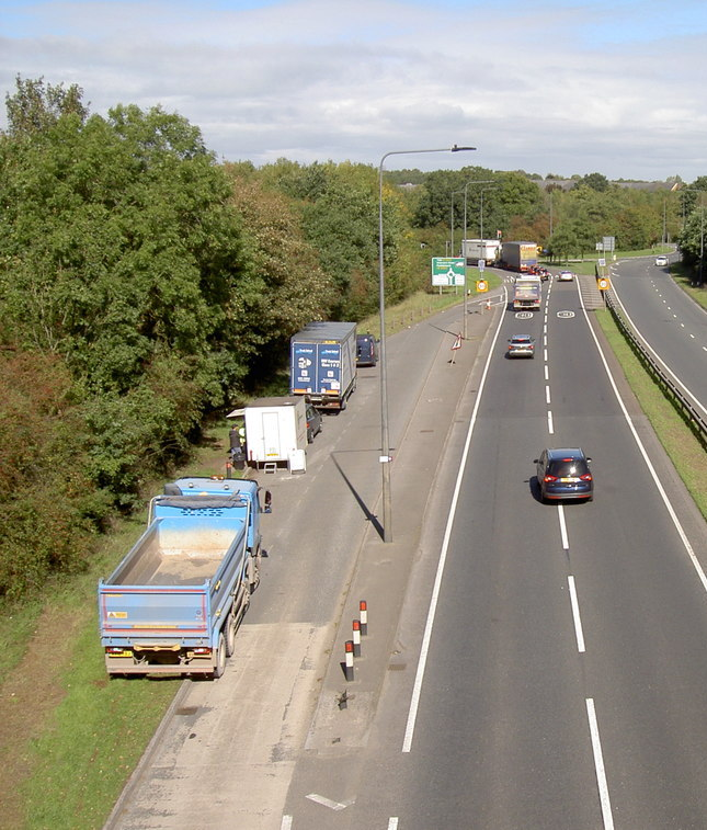 A two-lane dual carriageway approaching a roundabout with a lay-by with two trucks, a van and a snack wagon parked in it leaving almost no space. There are trees to the left of the lay-by.