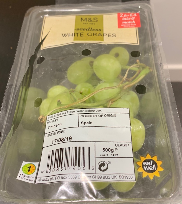 A clear plastic box of seedless white grapes, with the origin shown as Spain.